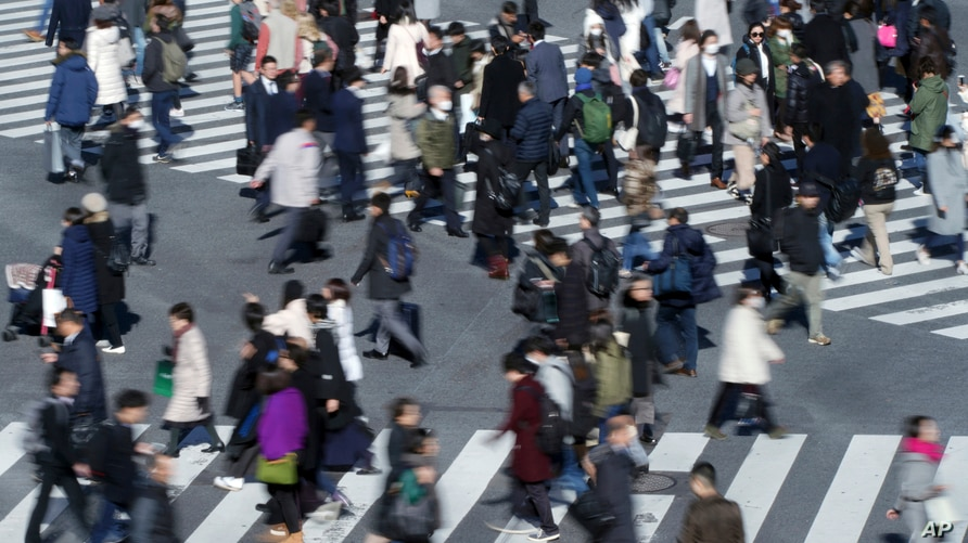 FILE - In this Jan. 11, 2018 photo, people walk on a pedestrian crossing at Shibuya district in Tokyo. The governor of Bank of…