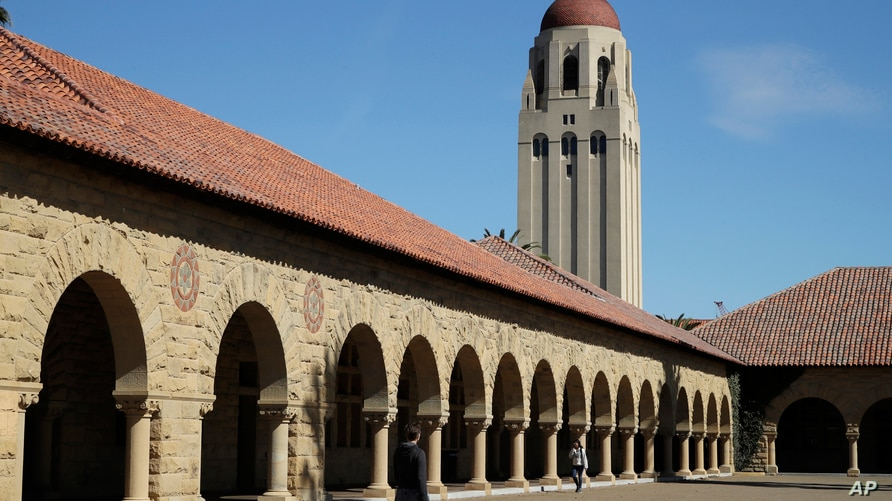 FILE- In this March 14, 2019, file photo, people walk on the Stanford University campus beneath Hoover Tower in Stanford, Calif…