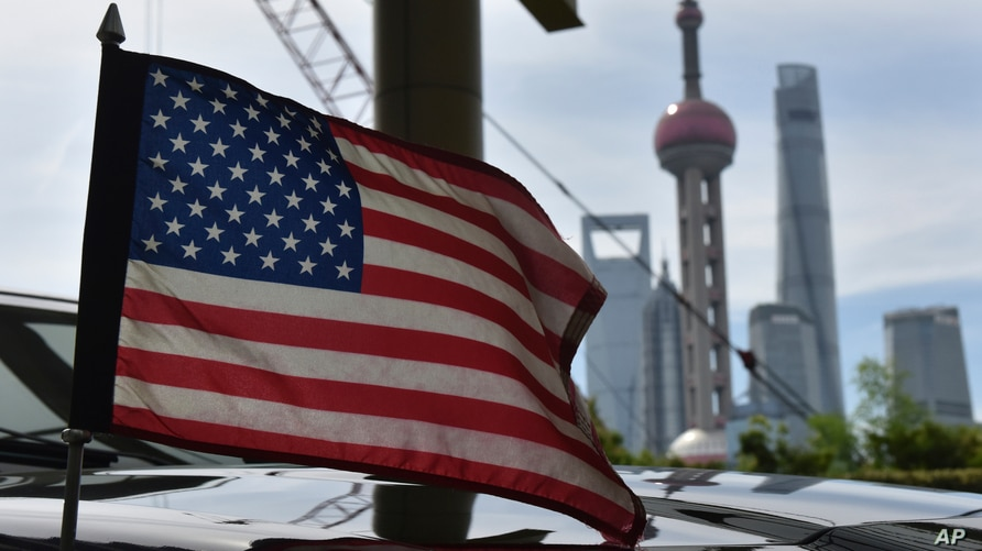 A U.S. flag flies on a U.S. consulate car, with the backdrop of buildings in the Lujiazui financial district, outside a hotel…