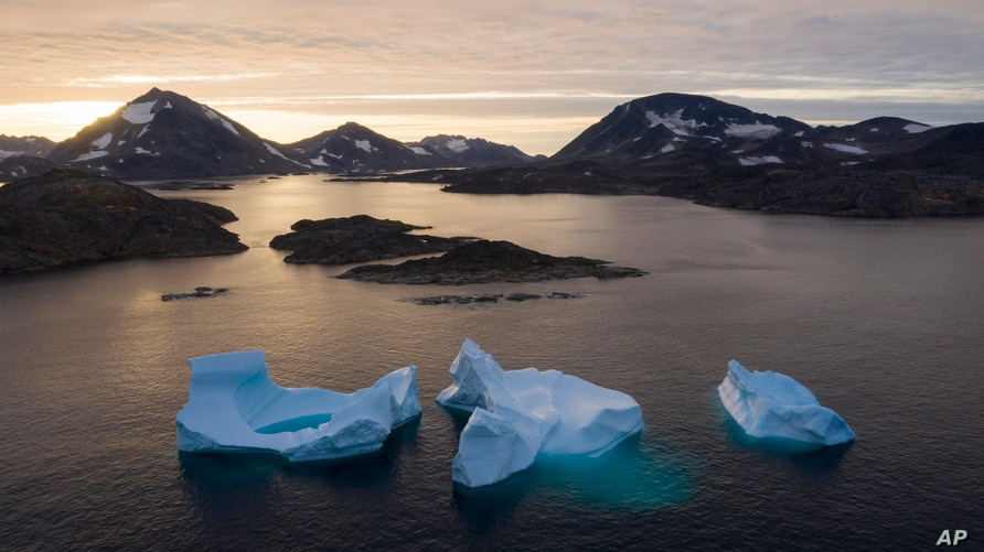 FILE - In this Aug. 16, 2019, file photo, large icebergs float away as the sun rises near Kulusuk, Greenland. Rising…
