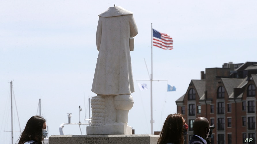 FILE - Passers-by walk near a damaged Christopher Columbus statue, Wednesday, June 10, 2020, in a waterfront park near the city's traditionally Italian North End neighborhood, in Boston.