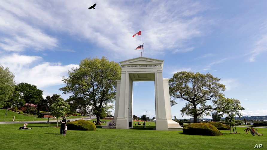 FILE - In this May 17, 2020, file photo, a bird flies from the U.S. into Canada over the Peace Arch in Peace Arch Historical…