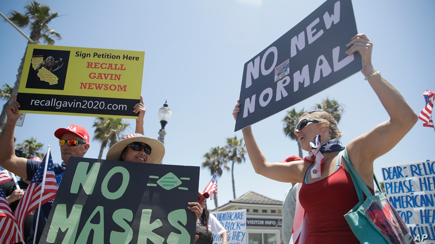 Demonstrators hold signs as they protest the lockdown and wearing masks June 27, 2020, in Huntington Beach, Calif.