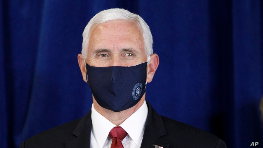 Vice President Pence wears a mask as he is introduced to speak to the Commissioned Corps of the U.S. Public Health Service