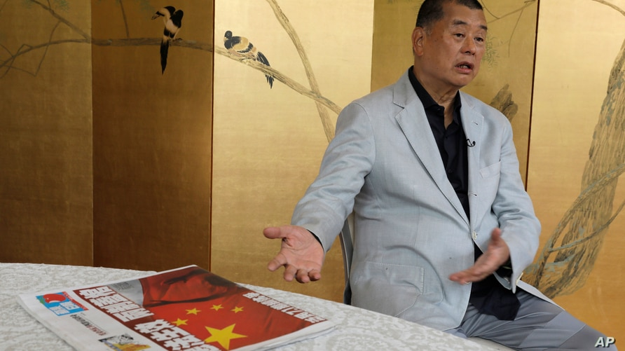 Hong Kong media tycoon Jimmy Lai gesture next to a copy of Apple Daily's July 1 edition during an interview Hong Kong, July 1, 2020.