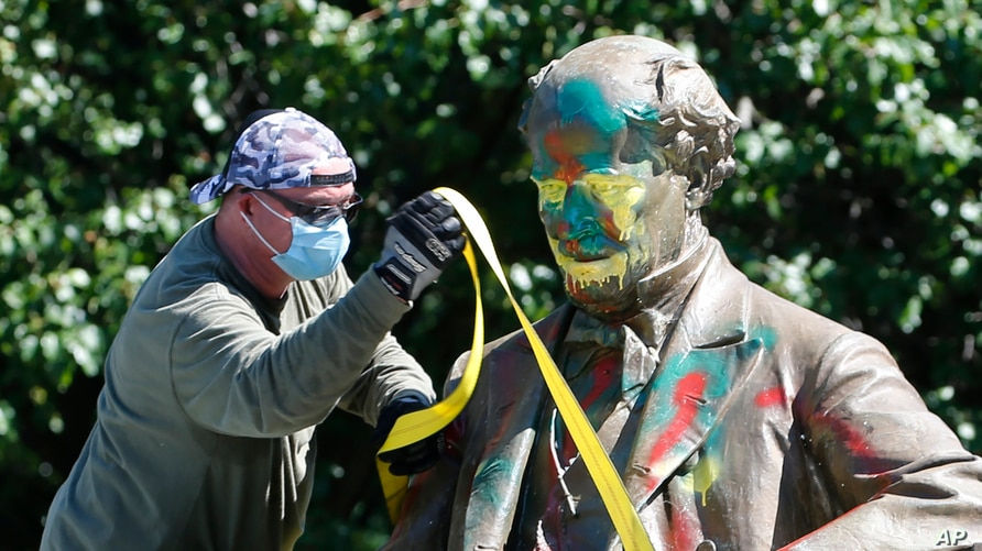 A worker secures the statue of Confederate Naval officer Matthew Fontaine Maury to a truck on Monument Avenue, Thursday, July 2…