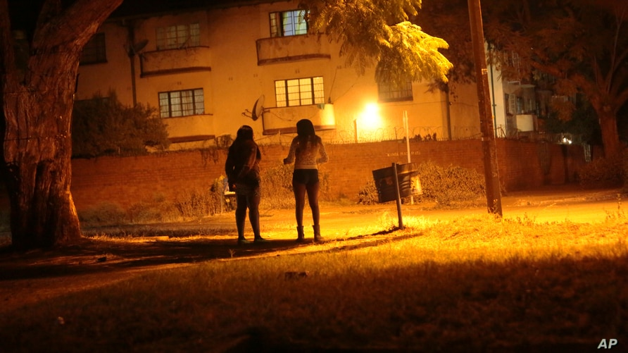 Sex workers wait for clients in the red light district of Harare, Zimbabwe, Friday, June 12, 2020. As the coronavirus spreads in Africa, it increasingly threatens those who earn their living on the streets, including sex workers with HIV.