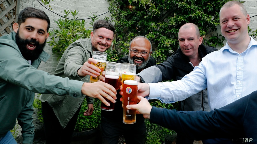 Men enjoy their first beers as the Chandos Arms pub reopens, in London, July 4, 2020.