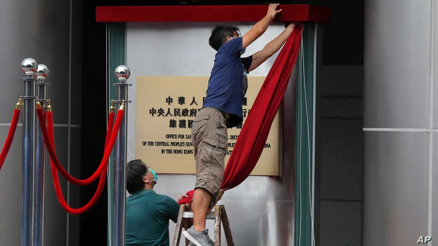 Workers take off a curtain after attend an opening ceremony for China's new Office for Safeguarding National Security in Hong Kong, July 8, 2020.
