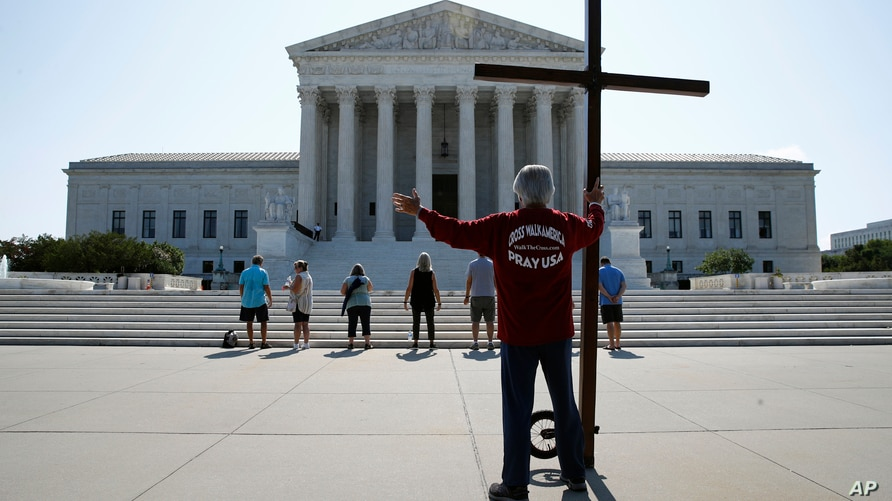 Tom Alexander holds a cross as he prays prior to rulings outside the Supreme Court on Capitol Hill in Washington, July 8, 2020.