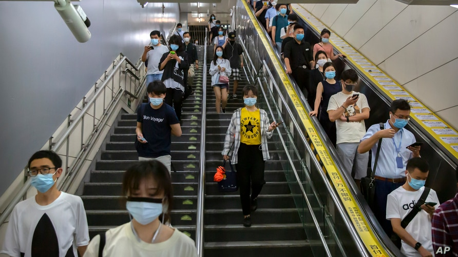 Commuters wearing face masks to protect against the spread of the new coronavirus walk through a subway station in Beijing, July 9, 2020.