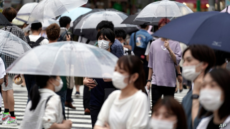 People wearing a protective face mask to help curb the spread of the coronavirus walk at Shibuya pedestrian crossing, July 9, 2020, in Tokyo.