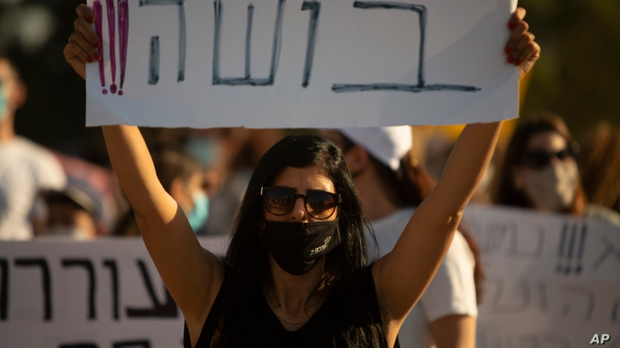 "An Israeli social worker holds a sign in Hebrew that reads, ""shame,"" during a protest against the economic situation in the central Israeli town of Kfar Ahim, July 9, 2020."