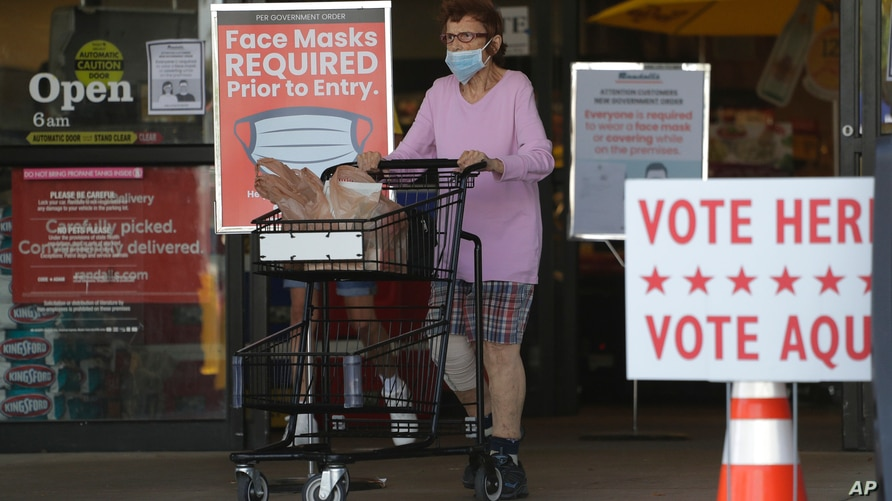 A shopper wearing a mask for protection against COVID-19 leaves a grocery store that is also searing as an early polling site,…