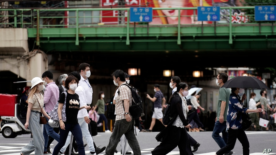 People wearing protective face masks to help curb the spread of the coronavirus walk at a pedestrian crossing Friday, July 10,…