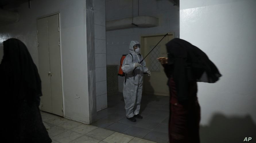 A member of a humanitarian aid agency disinfects inside Ibn Sina Hospital as prevention against the coronavirus in Idlib, Syria, March 19, 2020.