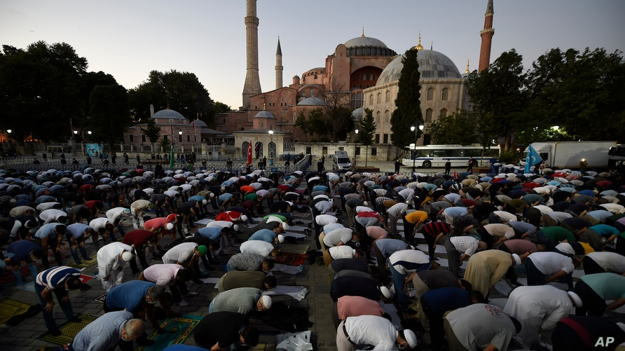 Muslims offer their evening prayers outside the Byzantine-era Hagia Sophia, one of Istanbul's main tourist attractions in the…