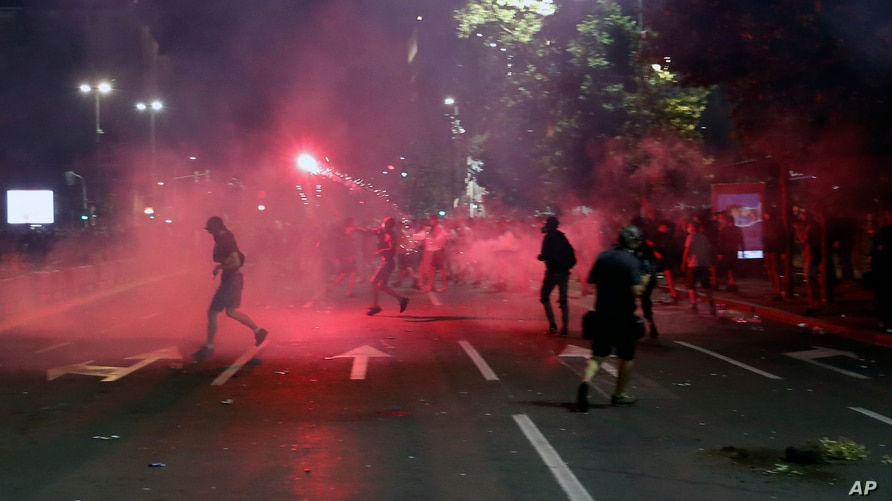 Protesters clash with riot police on the steps of the Serbian parliament during a protest in Belgrade, Serbia, July 10 2020.
