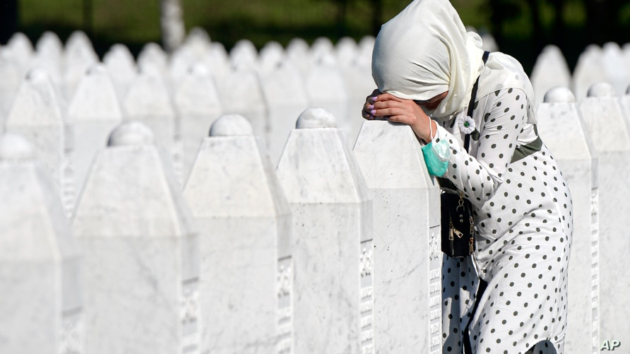 A woman leans on a grave stone in Potocari, near Srebrenica, Bosnia, July 11, 2020. Nine newly found and identified men and boys were laid to rest as Bosnians commemorate 25 years since more than 8,000 Bosnian Muslims perished in 10 days of slaughter.