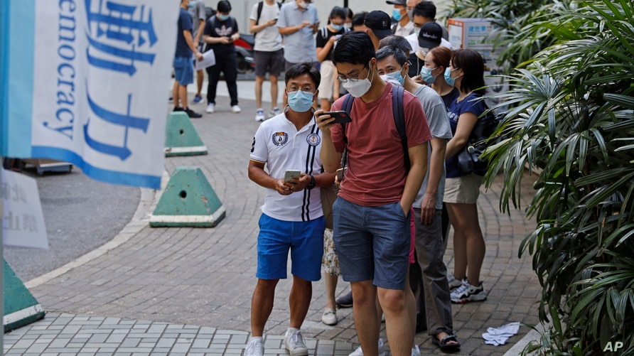"People wearing face masks queue up to vote in Hong Kong, July 11, 2020, in an unofficial ""primary"" for pro-democracy candidates ahead of legislative elections in September."