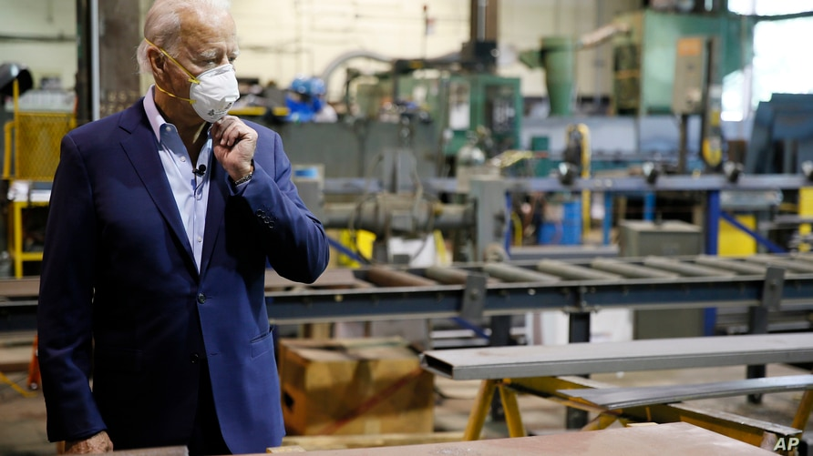 Democratic presidential candidate, former Vice President Joe Biden adjusts his mask during a tour of McGregor Industries, a metal fabricating facility in Dunmore, Pa, July 9, 2020.