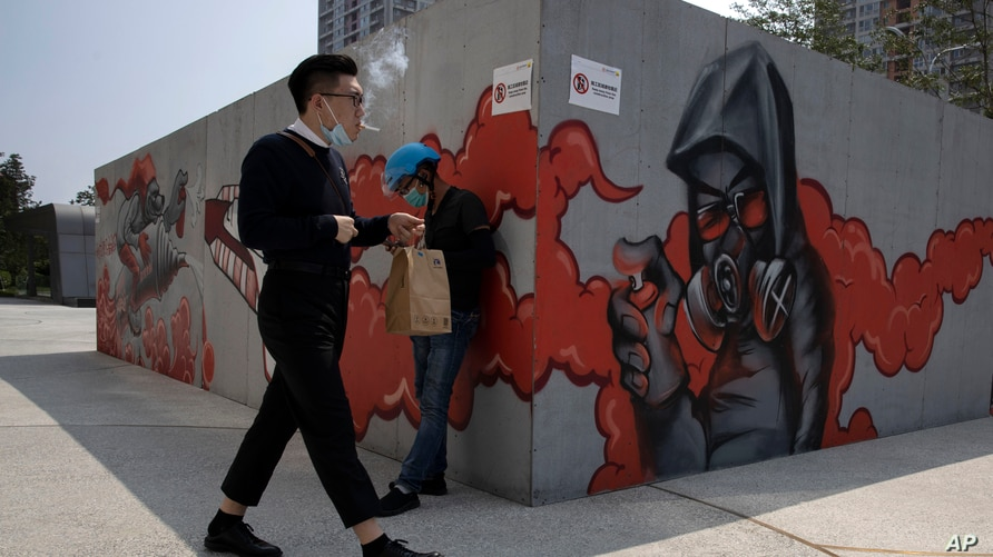 A man lowers his mask to smoke as he walks past graffiti artwork in Beijing Monday, July 13, 2020. China reported eight new…