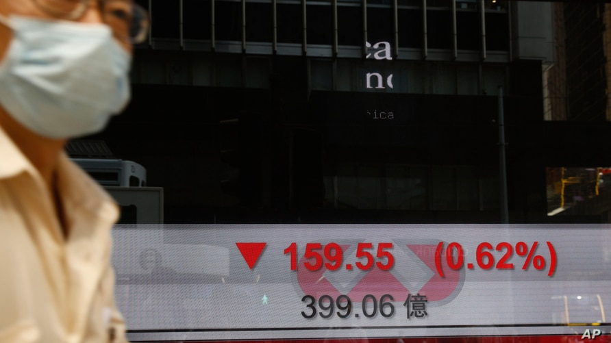A man wearing a face mask walks past a bank's electronic board showing the Hong Kong share index in Hong Kong, July 14, 2020.