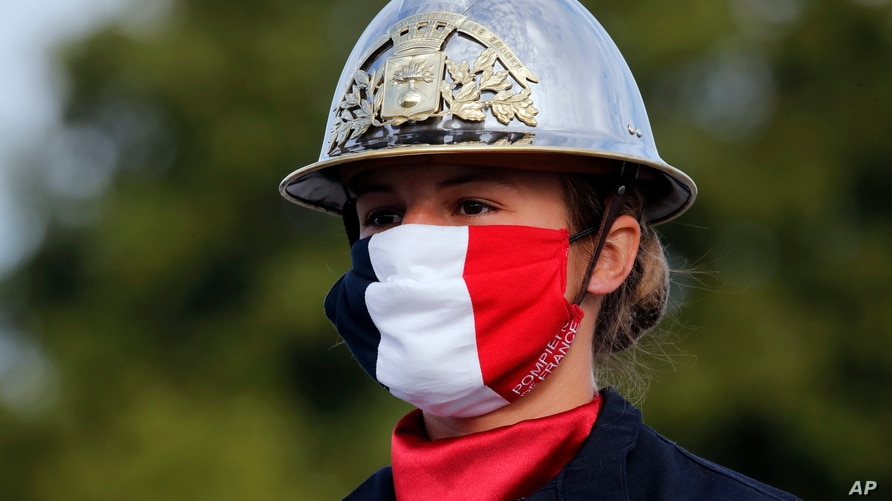 A firefighter wears a face mask with the colors of the French flag, prior to the Bastille Day parade, July 14, 2020 on the Champs Elysees avenue in Paris.