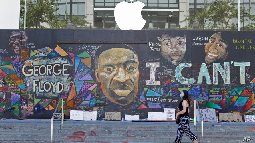 A pedestrian walks past a boarded-up Apple store that's been covered in street art in downtown Portland, Ore., Monday, July 13,…