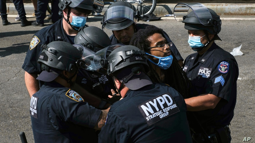 A Black Lives Matter protester is apprehended by NYPD officers on Brooklyn Bridge, Wednesday, July 15, 2020, in New York…
