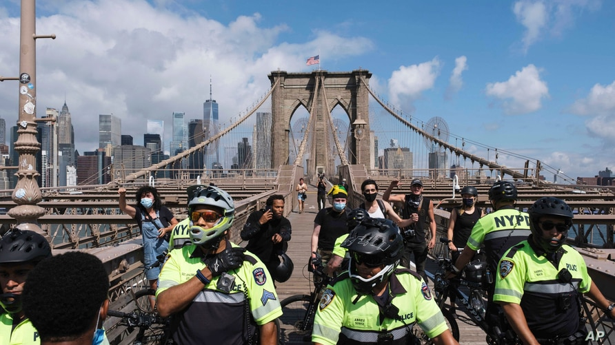 NYPD officers block the Brooklyn Bridge after the clash between officers and Black Lives Matter protesters, Wednesday, July 15,…