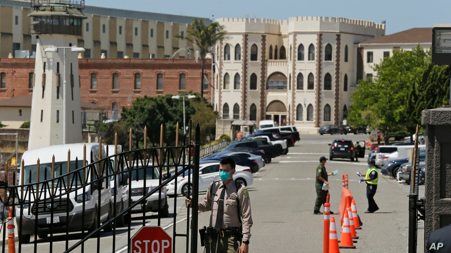 A correctional officer closes the main gate at San Quentin State Prison in San Quentin, Calif, July 9, 2020.