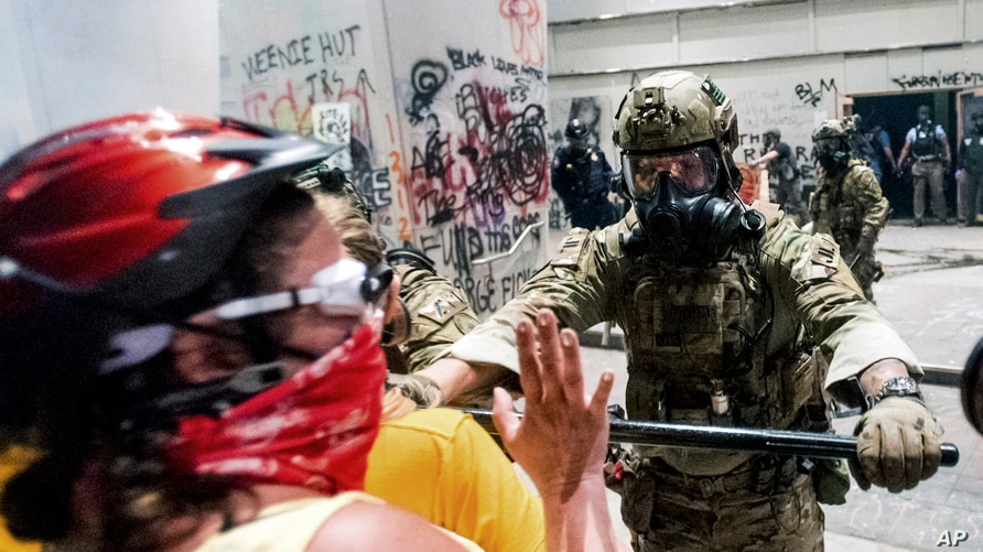 A federal officer pushes back demonstrators at the Mark O. Hatfield United States Courthouse on Tuesday, July 21, 2020, in…