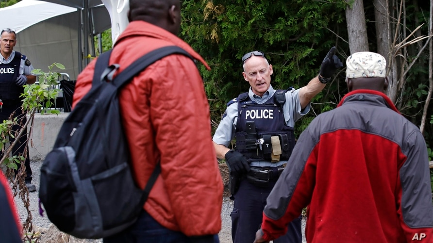 FILE - In this Aug. 7, 2017, file photo, Royal Canadian Mounted Police officers greet migrants as they enter into Canada at an…