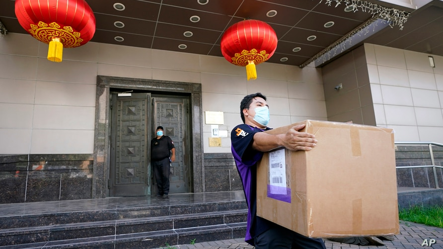 """A FedEx employee removes a box from the Chinese Consulate Thursday, July 23, 2020, in Houston. China says """"malicious slander""""…"""