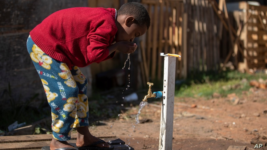 A boy brushes his teeth from a communal faucet in the Jardim Julieta squatter camp in Sao Paulo, Brazil, July 23, 2020.