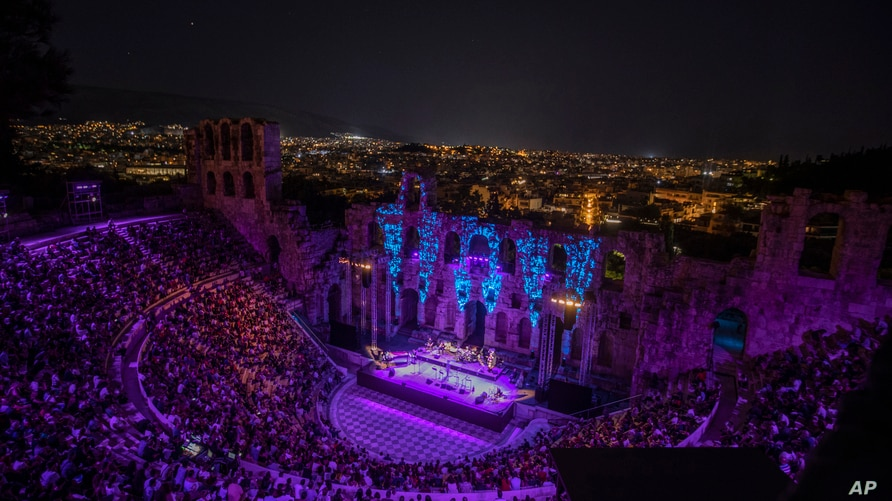 Spectators listen a concert at Odeon of Herodes Atticus as the city of Athens is seen on the background, July 15, 2020.
