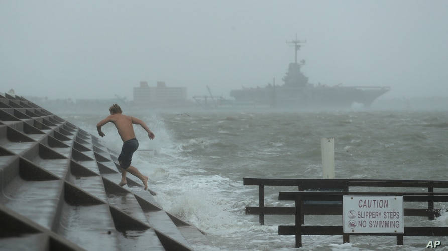A man jumps from a wave as Hurricane Hanna begins to make landfall, Saturday, July 25, 2020, in Corpus Christi, Texas.   The…