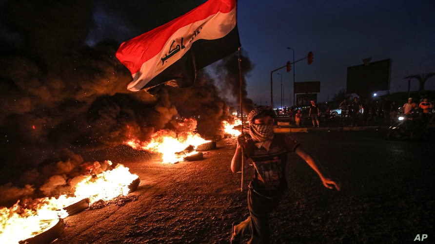 A protester runs holding an Iraqi flag as tires burn during a demonstration demanding better public services and jobs in Basra,…