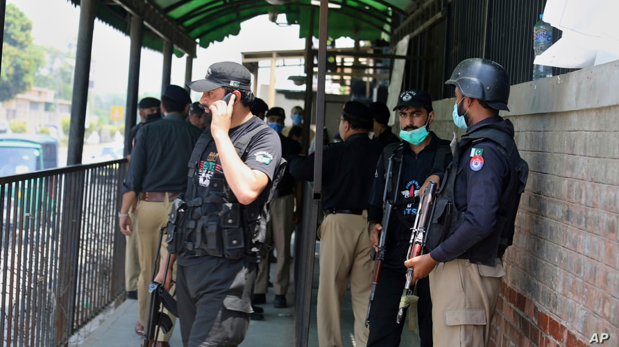 Police officers gather at an entry gate of district court following the killing of Tahir Shamim Ahmad, who was in court accused…