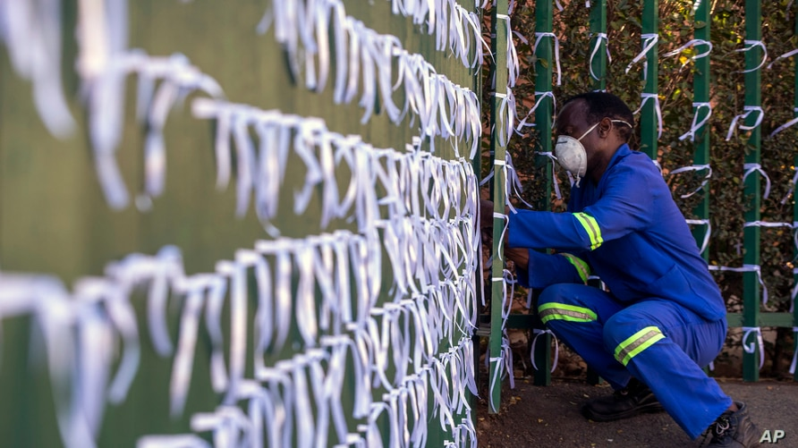 Silva Cossa, the caretaker, ties ribbons onto the fence to represents a South African who has died from Covid-19, at St James…