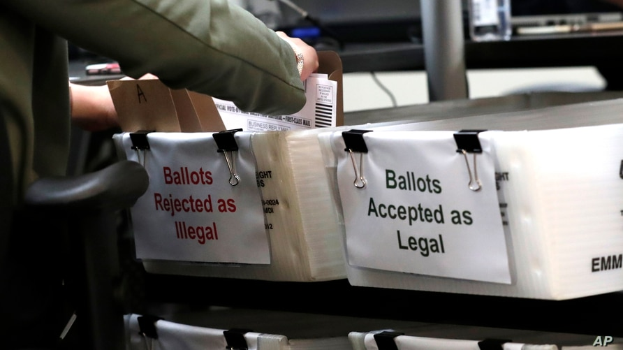 A Miami-Dade County Elections Department employee places a vote-by-mail ballot for the August 18 primary election into a box…
