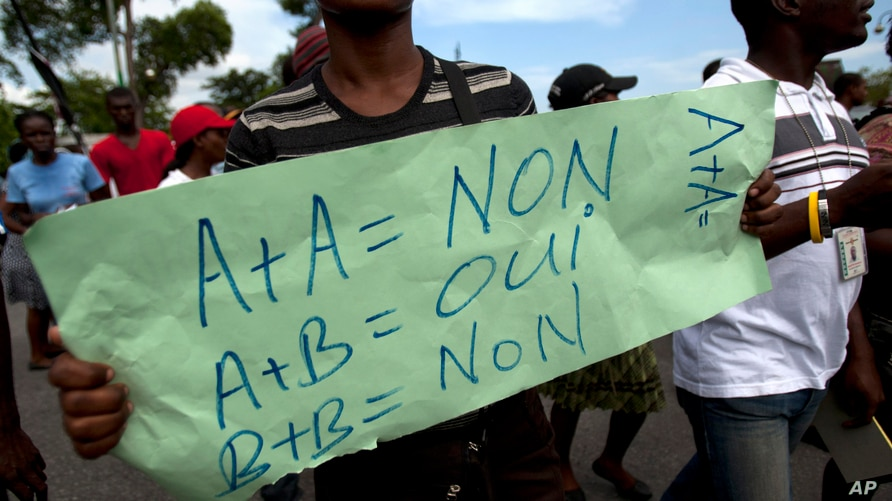 """A protester holds a sign that reads in French """"A+A=No. A+B=Yes. B+B=No"""" during an anti-gay demonstration in Port-au-Prince."""