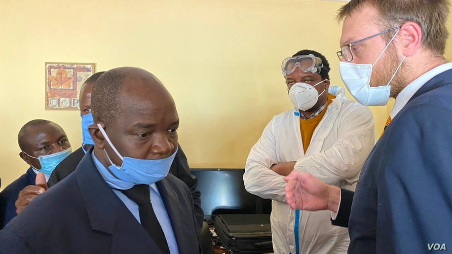 Detective Inspector Morgan Chafa (left) arguing with Doug Coltart of Zimbabwe Lawyers for Human Rights (right) while prominent journalist Hopewell Chin'ono (in PPEs) looks on July 21, 2020 in Harare. (VOA/Columbus Mavhunga)