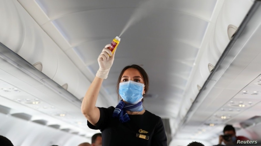 A flight attendant wearing a face mask sprays disinfectant inside a plane at Sharm el-Sheikh International Airport, Egypt, following the outbreak of COVID-19, June 20, 2020. (REUTERS)