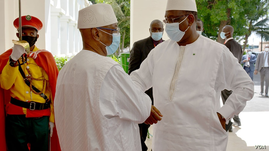 Mali's President Ibrahim Boubacar Keita, at right, and Senegal's President Macky Sall exchange COVID-era greetings at the Sheraton Bamako Hotel in the Malian capital, July 23, 2020. (Photo by Modibo Dembele/VOA)