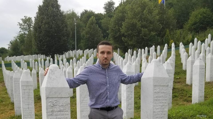 Behidin Piric, a survivor of the Srebrenica Genocide of 1995, stands next to the graves of his grandfather and great-uncles.