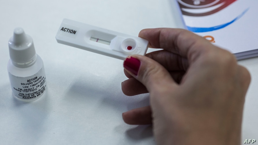 FILE - A woman demonstrates how an HIV self-test kit works, in Rio de Janeiro, Brazil, July 07, 2017.