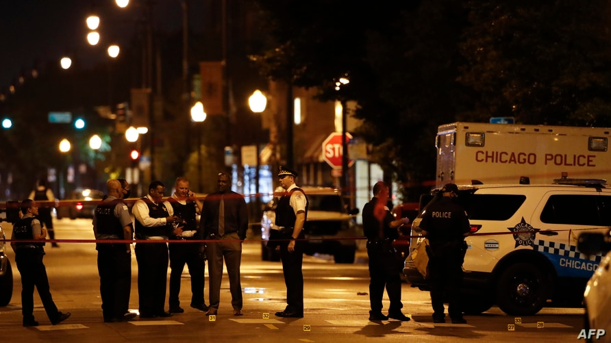 Police officers investigate at the scene of a shooting outside a funeral home in Chicago, Illinois, July 21, 2020.