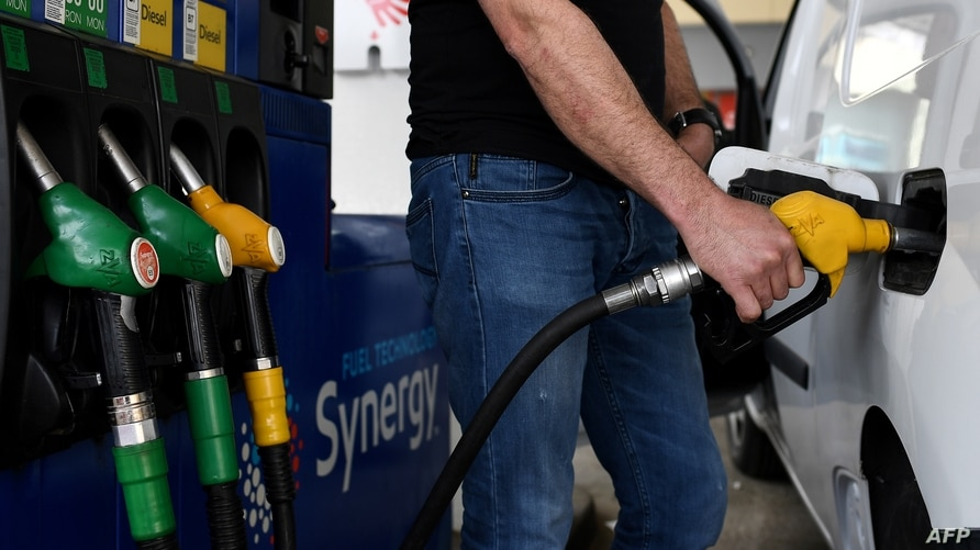 FILE - a man refuels his car at a petrol filling station in Paris, France, on the 32nd day of a strict lockdown aimed at curbing the spread of the COVID-19 pandemic, April 17, 2020.